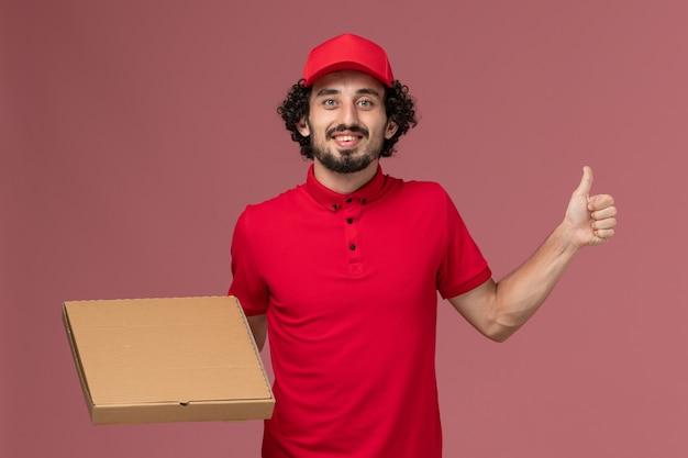 Widok z przodu mężczyzna dostawy kurierskiej mężczyzna w czerwonej koszuli i pelerynie gospodarstwa pudełko z jedzeniem dostawy na różowej ścianie pracownik firmy kurierskiej pracy mężczyzna