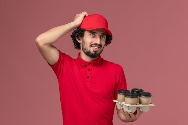 Widok z przodu mężczyzna dostawy kurierskiej mężczyzna w czerwonej koszuli i pelerynie, trzymając brązowe filiżanki kawy dostawy na jasnoróżowej ścianie