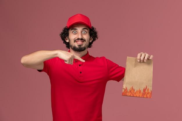 Widok z przodu mężczyzna dostawy kurierskiej mężczyzna w czerwonej koszuli i pelerynie, trzymając pakiet żywności na różowej ścianie pracownik pracownik firmy dostarczającej usługi