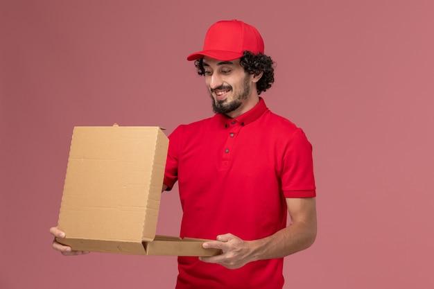 Widok z przodu mężczyzna dostawy kurierskiej mężczyzna w czerwonej koszuli i pelerynie, trzymając puste pole pożywienia na różowej ścianie praca pracownika firmy dostawy usług