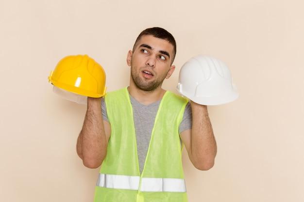 Widok z przodu mężczyzna konstruktor trzymając kaski myśli na jasnym tle