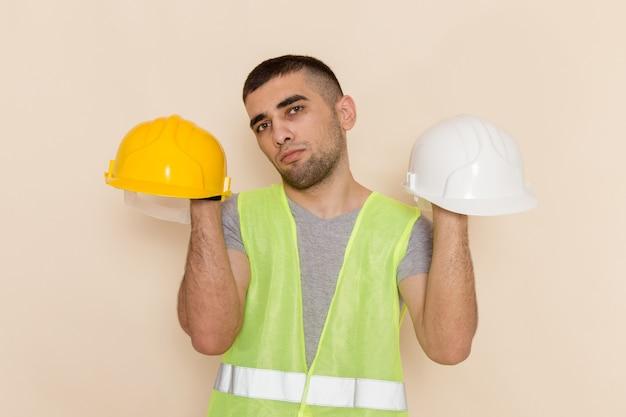 Widok z przodu mężczyzna konstruktor trzymając kaski na jasnym tle