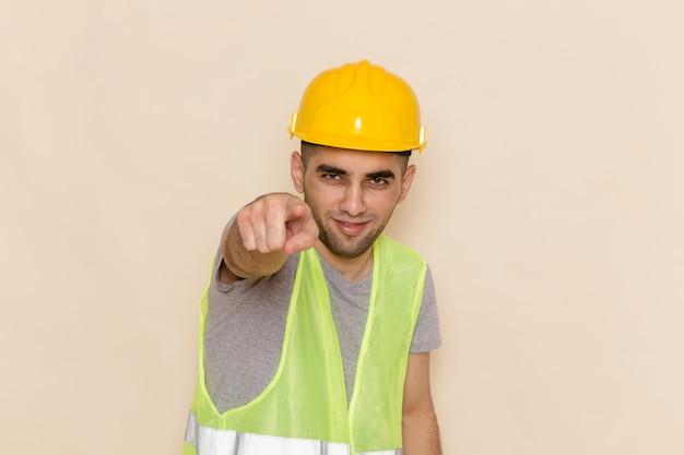 Widok z przodu mężczyzna konstruktora w żółtym kasku, wskazując na jasnym tle