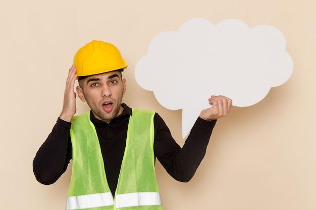 Widok z przodu mężczyzna konstruktora w żółtym kasku z dużym białym znakiem na jasnym tle
