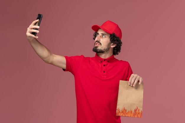 Widok z przodu mężczyzna kurier dostawy mężczyzna w czerwonej koszuli i pelerynie, trzymając pakiet żywności i biorąc selfie na różowej ścianie pracownik dostawy usług