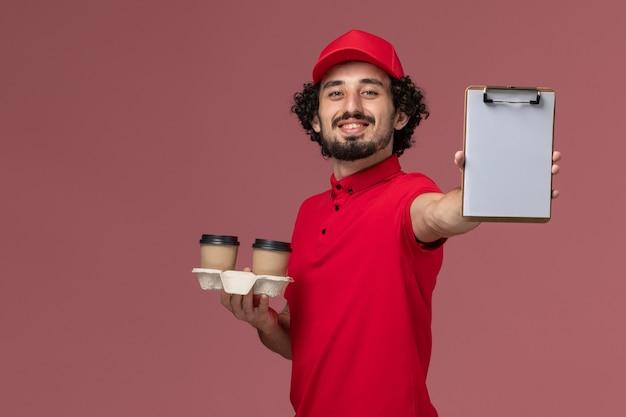 Widok z przodu mężczyzna kurier w czerwonej koszuli i pelerynie trzymający brązowe filiżanki do kawy i notatnik na jasnoróżowej ścianie pracownik dostawy usług