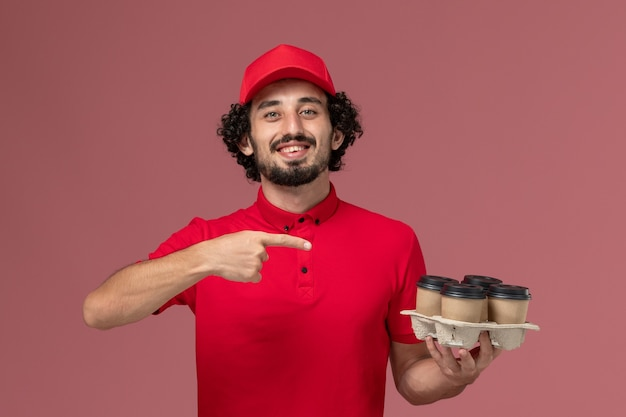 Widok z przodu mężczyzna kurier w czerwonej koszuli i pelerynie trzymający brązowe filiżanki do kawy na jasnoróżowej ścianie usługa dostawy pracownik firma mężczyzna mężczyzna
