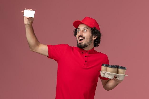 Widok z przodu mężczyzna kurier w czerwonej koszuli i pelerynie trzymający brązowe kubki do kawy z plastikową kartą na różowej ścianie pracownik usługi dostawy mężczyzna mężczyzna