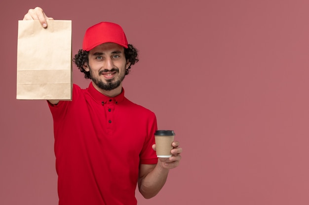 Widok z przodu mężczyzna kurier w czerwonej koszuli i pelerynie trzymający brązowy kubek kawy i pakiet żywności na jasnoróżowej ścianie usługa dostawy praca praca pracownika