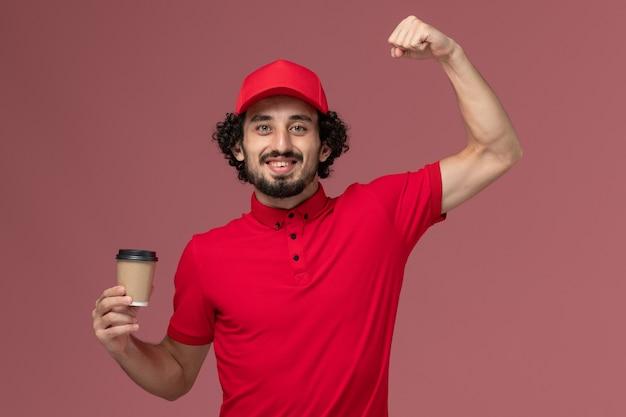 Widok z przodu mężczyzna kurier w czerwonej koszuli i pelerynie trzymający brązowy kubek kawy zginający się na jasnoróżowej ścianie mundurowy pracownik dostawy