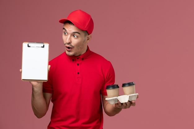 Widok z przodu mężczyzna kurier w czerwonym mundurze, trzymając brązowe filiżanki kawy dostawy i notatnik na jasnoróżowej ścianie pracownika pracy mężczyzna