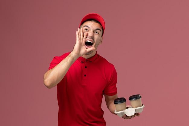 Widok z przodu mężczyzna kurier w czerwonym mundurze, trzymając brązowe filiżanki kawy dostawy krzycząc na różowej ścianie pracownik płci męskiej