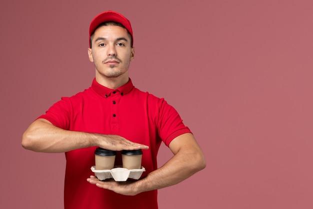 Widok z przodu mężczyzna kurier w czerwonym mundurze, trzymając brązowe filiżanki kawy dostawy na różowej ścianie pracownika