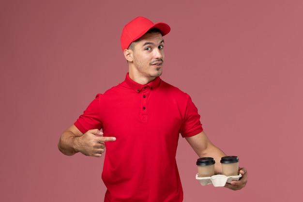 Widok z przodu mężczyzna kurier w czerwonym mundurze, trzymając brązowe filiżanki kawy dostawy na różowym biurku
