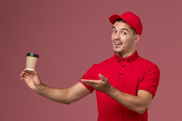 Widok z przodu mężczyzna kurier w czerwonym mundurze, trzymając filiżankę kawy dostawy na jasnoróżowej ścianie pracownik płci męskiej