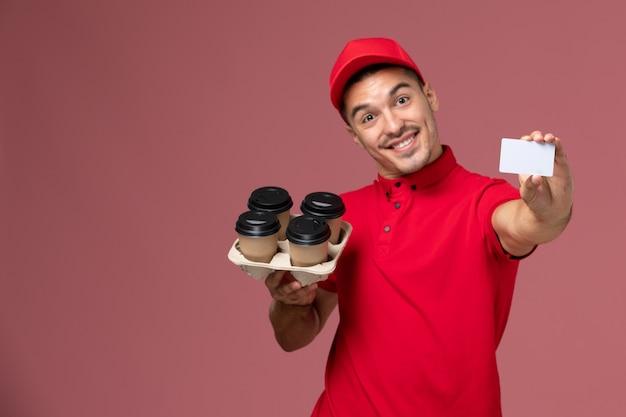 Widok z przodu mężczyzna kurier w czerwonym mundurze, trzymając filiżanki kawy dostawy z białą kartą, uśmiechając się na różowej ścianie
