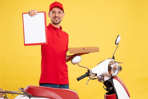 Widok z przodu mężczyzna kurier w czerwonym mundurze z pudełkiem na żywność na żółtym kolorze dostawa pracownik rower mundur pracy praca serwisowa