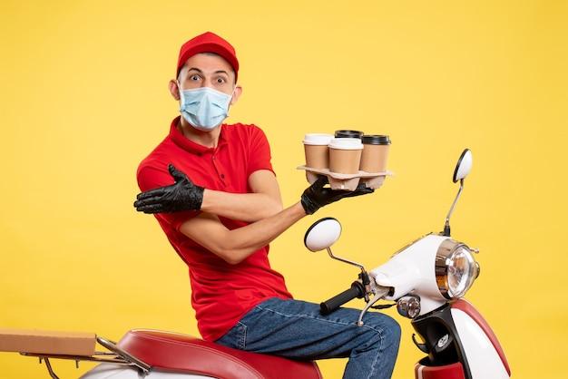 Widok z przodu mężczyzna kurier w mundurze i masce z kawą na żółtym stanowisku gastronomicznym covid-wirus pandemia kolorów pracy