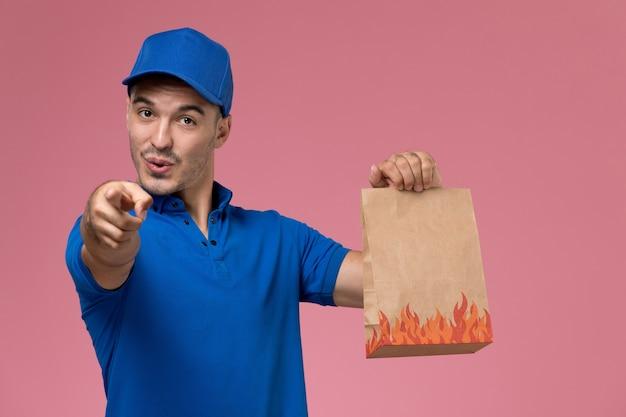 Widok z przodu mężczyzna kurier w niebieskim mundurze, trzymając pakiet żywności, wskazując na różową ścianę, świadczenie usług w mundurze pracownika