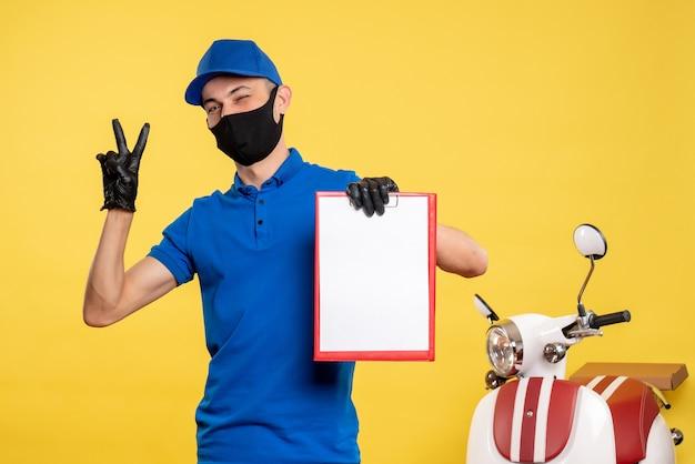 Widok z przodu mężczyzna kurier w niebieskim mundurze, trzymający kartotekę na żółto, służba pracy covid- pandemic color uniform work