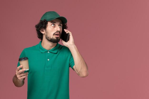 Widok z przodu mężczyzna kurier w zielonym mundurze i pelerynie, trzymając filiżankę kawy i rozmawiając przez telefon na różowym tle jednolita usługa dostawy