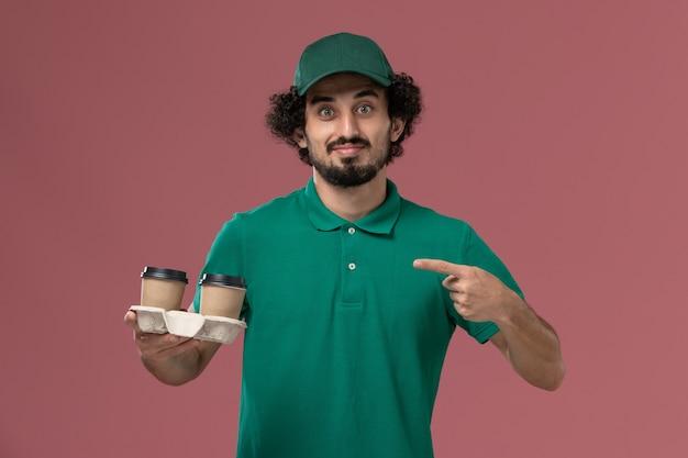Widok z przodu mężczyzna kurier w zielonym mundurze i pelerynie trzymając filiżanki kawy na różowym tle jednolite usługi dostawy praca pracownik mężczyzna pracy