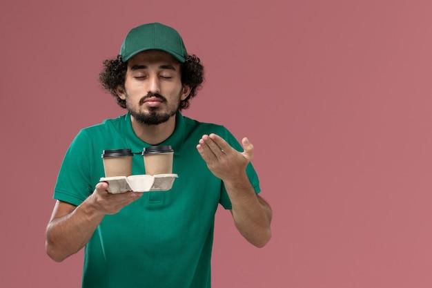 Widok z przodu mężczyzna kurier w zielonym mundurze i pelerynie, trzymając filiżanki kawy na różowym tle, mundur usługowy pracownik pracy