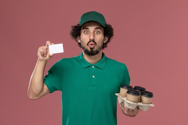 Widok z przodu mężczyzna kurier w zielonym mundurze i pelerynie, trzymając filiżanki z kawą z kartą na różowym tle