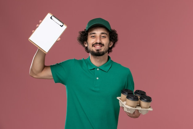 Widok z przodu mężczyzna kurier w zielonym mundurze i pelerynie, trzymając filiżanki z notatnikiem na różowym tle, jednolita praca pracownika dostawy