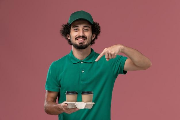 Widok z przodu mężczyzna kurier w zielonym mundurze i pelerynie trzymający filiżanki z kawą na różowym tle jednolita usługa dostawy