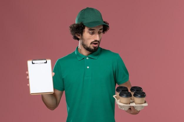 Widok z przodu mężczyzna kurier w zielonym mundurze i pelerynie trzymający filiżanki z kawą z notatnikiem na różowym tle usługa jednolita praca dostawy mężczyzna