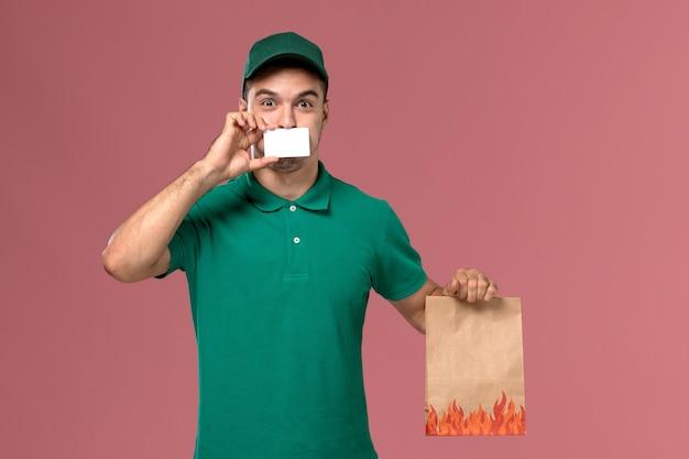 Widok z przodu mężczyzna kurier w zielonym mundurze, trzymając pakiet żywności i kartę na różowym tle
