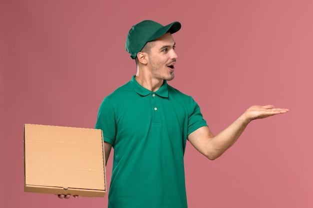 Widok z przodu mężczyzna kurier w zielonym mundurze, trzymając pudełko na żywność na różowym tle