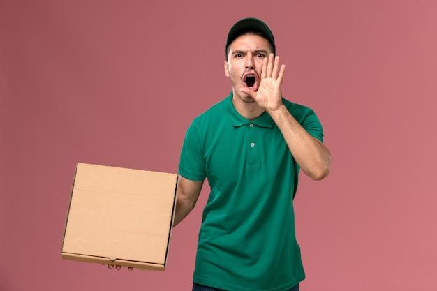 Widok z przodu mężczyzna kurier w zielonym mundurze trzymając pudełko z jedzeniem krzycząc na różowym tle
