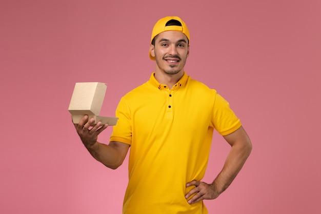 Widok z przodu mężczyzna kurier w żółtym mundurze i pelerynie, trzymając i otwierając mały pakiet żywności dostawy uśmiechnięty na różowym tle.