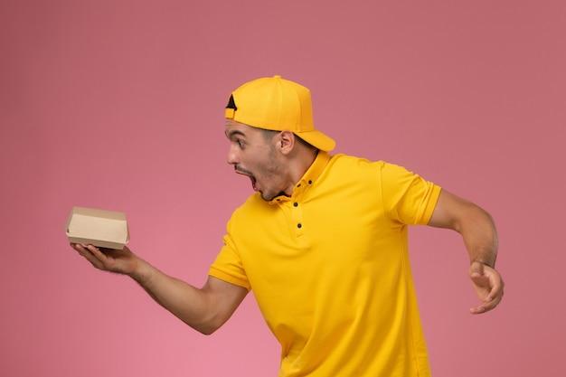 Widok z przodu mężczyzna kurier w żółtym mundurze i pelerynie trzymający małą paczkę z dostawą żywności przestraszony na jasnoróżowym tle.