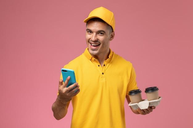 Widok z przodu mężczyzna kurier w żółtym mundurze, trzymając filiżanki kawy dostawy za pomocą telefonu, śmiejąc się na różowym tle
