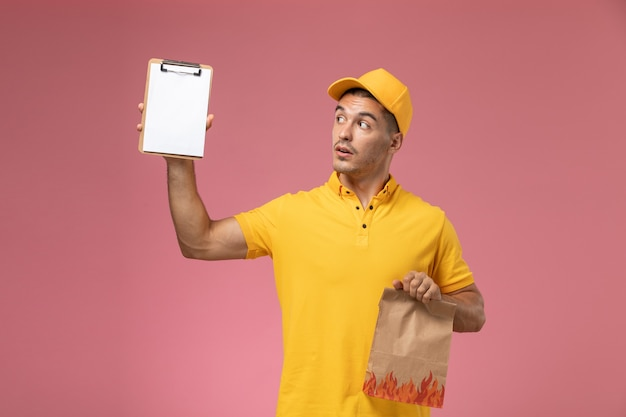 Widok z przodu mężczyzna kurier w żółtym mundurze, trzymając notatnik i pakiet żywności na różowym biurku