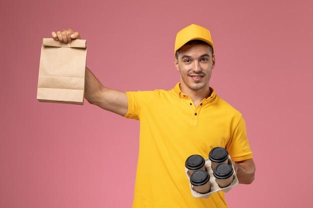 Widok z przodu mężczyzna kurier w żółtym mundurze, trzymając pakiet żywności i filiżanki kawy dostawy, uśmiechając się na różowym tle