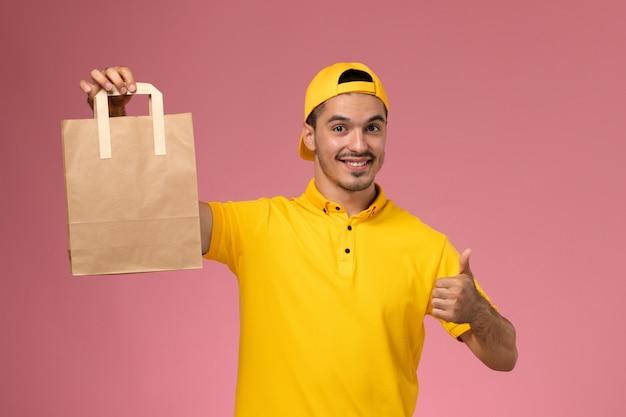 Widok z przodu mężczyzna kurier w żółtym mundurze trzymając papierowy pakiet dostawy uśmiechnięty na jasnoróżowym tle.