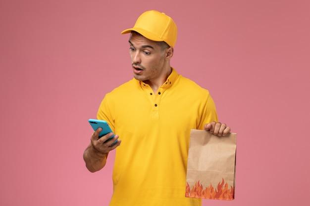 Widok z przodu mężczyzna kurier w żółtym mundurze za pomocą swojego telefonu trzymając pakiet żywności na różowym biurku