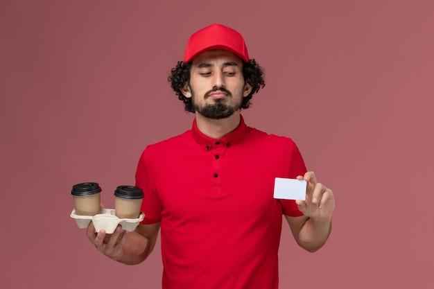 Widok z przodu mężczyzna kurierski mężczyzna w czerwonej koszuli i pelerynie trzymający brązowe filiżanki do kawy i kartę na jasnoróżowej ścianie pracownik dostawy mężczyzna mężczyzna