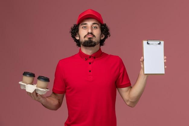 Widok z przodu mężczyzna kurierski w czerwonej koszuli i pelerynie trzymający brązowe kubki do kawy i notatnik na jasnoróżowej ścianie pracownik dostawy usług