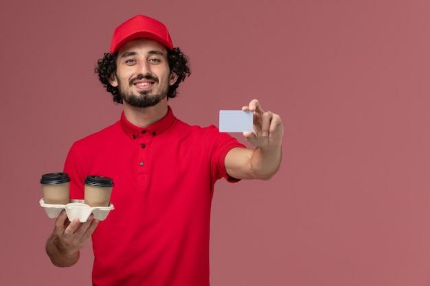 Widok z przodu mężczyzna kurierski w czerwonej koszuli i pelerynie trzymający brązowe kubki do kawy i szarą kartę na jasnoróżowej ścianie pracownik dostawy usług