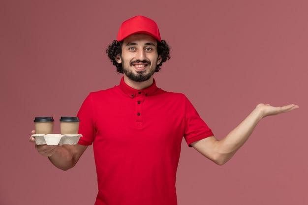 Widok z przodu mężczyzna kurierski w czerwonej koszuli i pelerynie trzymający brązowe kubki do kawy na jasnoróżowej ścianie usługa dostawy pracownik mężczyzna praca