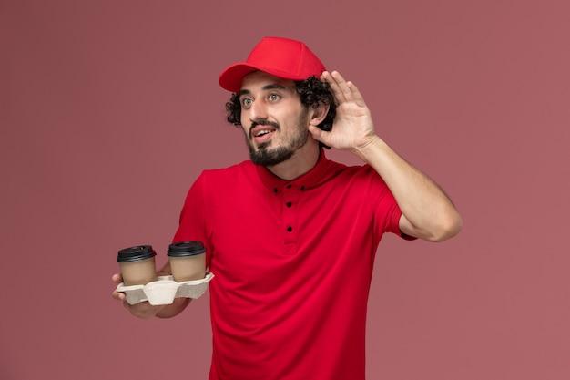 Widok z przodu mężczyzna kurierski w czerwonej koszuli i pelerynie trzymający brązowe kubki do kawy, próbujący usłyszeć na jasnoróżowej ścianie pracownik dostawy usług