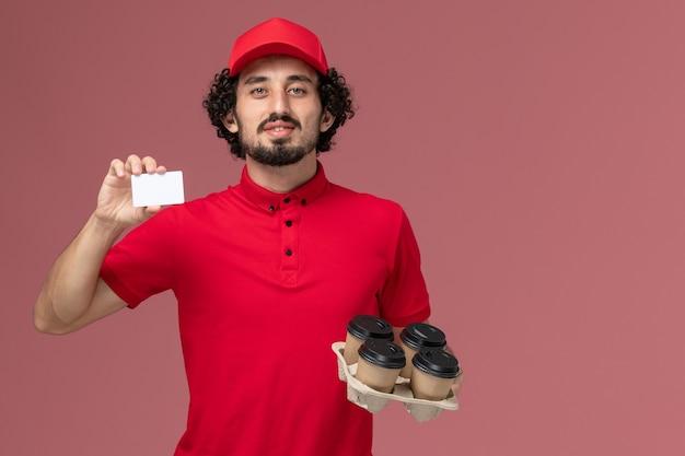 Widok z przodu mężczyzna kurierski w czerwonej koszuli i pelerynie trzymający brązowe kubki do kawy z plastikową kartą na różowej ścianie pracownik dostawy usług