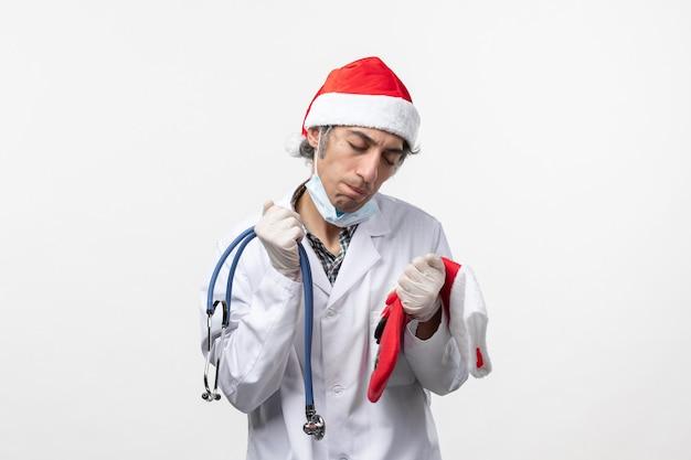 Widok z przodu mężczyzna lekarz czuje się zmęczony na białej ścianie wirus covid wakacje zdrowie
