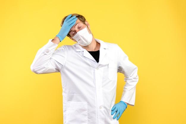 Widok z przodu mężczyzna lekarz czuje się zmęczony na żółtym tle pandemia covid health medic