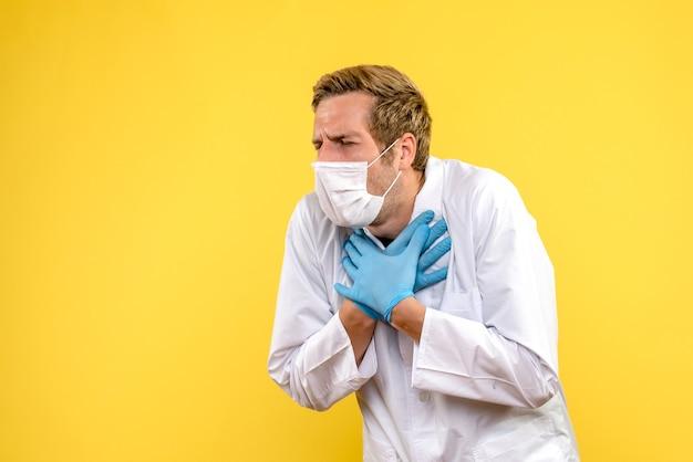 Widok z przodu mężczyzna lekarz mający problemy z oddychaniem na żółtym tle medyk pandemiczny zdrowia covid-